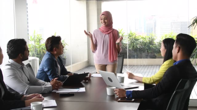 malaysian woman in hijab talking to colleagues - malaysian ethnicity stock videos & royalty-free footage