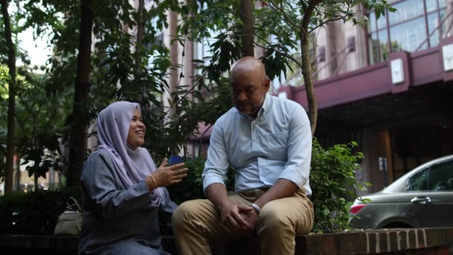 malaysian woman wearing hijab consoling a senior adult man - care stock videos & royalty-free footage
