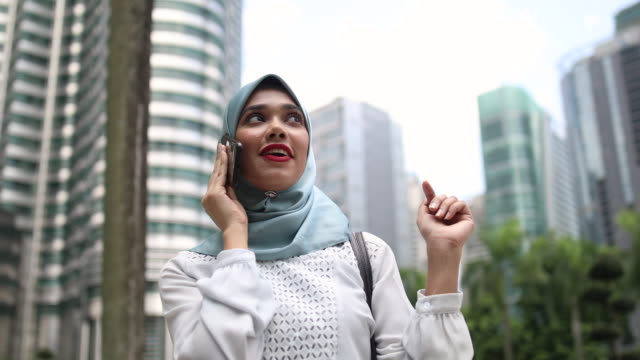 Malaysian woman wearing hijab, talking on the phone in the city