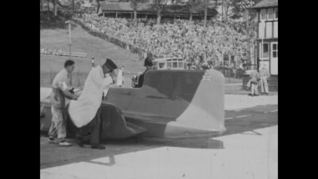 vídeos de stock, filmes e b-roll de malcolm campbell demonstrating his newly built one off campbellnapierrailton blue bird in front of crowds at brooklands race track in 1931 - carro foguete