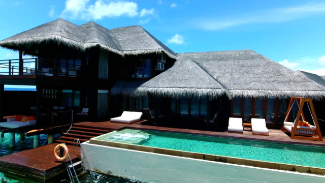 maldives, blue sky, turquoise sea, white sand and green palm trees. - holiday villa stock videos & royalty-free footage