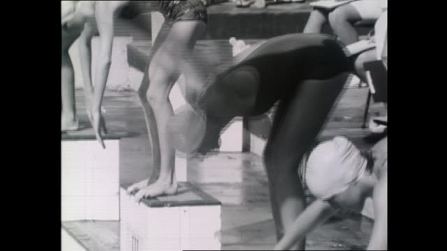 Swimmers dive in off the blocks / spectators officials including coach with stop watch Vic Arneil / Mike Wenden winning race / Shane Gould on the...
