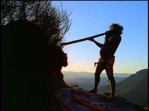 vídeos y material grabado en eventos de stock de silhouette male aborigine playing a didgeridoo / mountains in background / blue mountains, nsw, australia - instrumento de viento