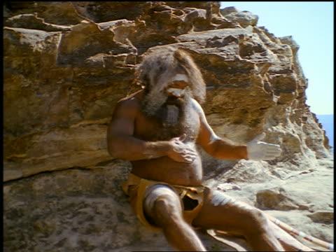 male aborigine sitting on rock painting stomach white / blue mountains, nsw, australia - australian aborigine culture stock videos & royalty-free footage