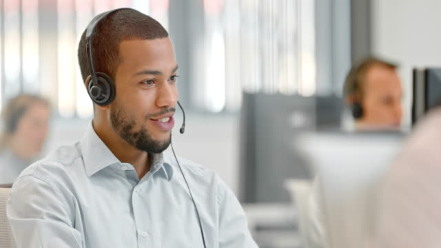 tu male african american telephone operator answering a call - customer service representative stock videos & royalty-free footage