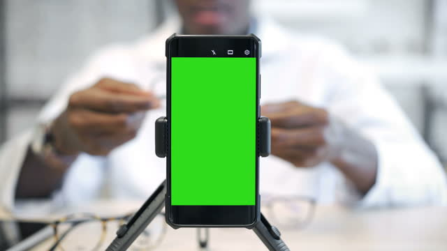 male african optometrist using smart phone with green screen monitor vlogging - keyable stock videos & royalty-free footage
