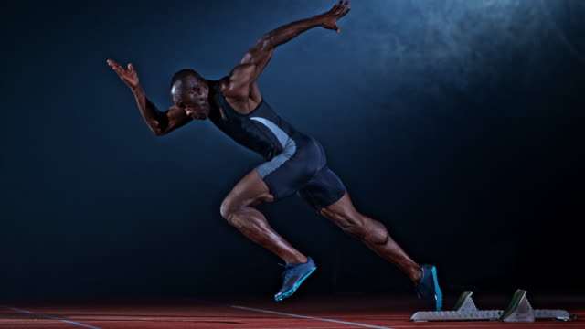 slo mo ts male african-american sprinter starting and running on a black misty background - atletico video stock e b–roll