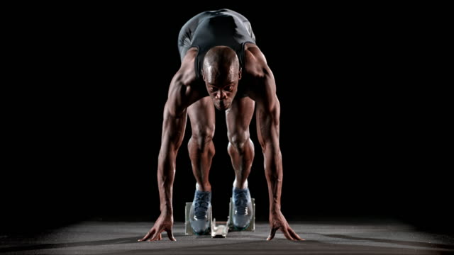 slo mo ld male african-american sprinter starting from the starting blocks - front view stock videos & royalty-free footage