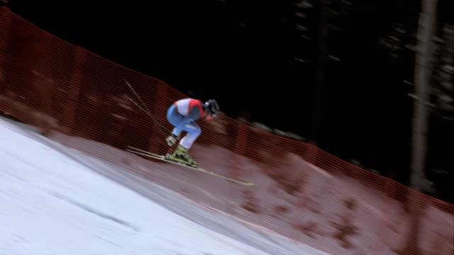 TS Male alpine skier doing a long jump in a downhill race