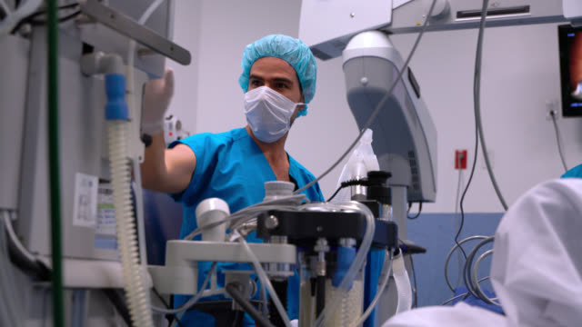 male anaesthesiologist checking the patients vitals during an eye surgery - anesthetic stock videos & royalty-free footage