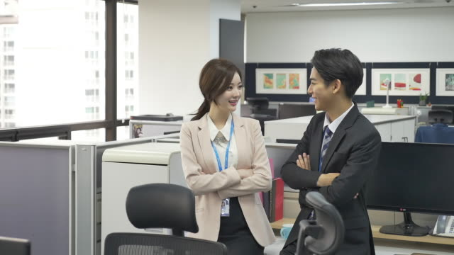 a male and a female employees having a conversation - シャツとネクタイ点の映像素材/bロール