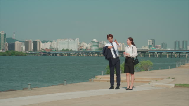 a male and a female office workers looking around in the han river park - hemd und krawatte stock-videos und b-roll-filmmaterial