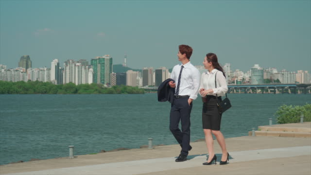 a male and a female office workers walking in the han river park - hemd und krawatte stock-videos und b-roll-filmmaterial
