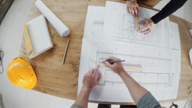 POV Male and female architect discussing and drawing alterations to a construction plan