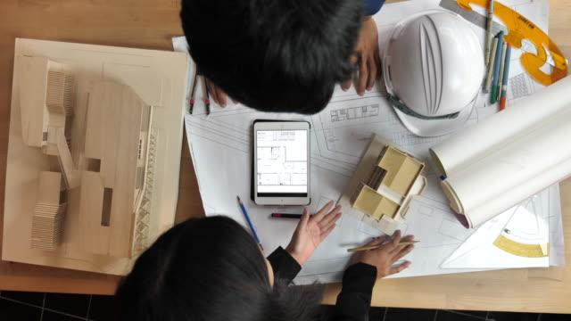 männliche und weibliche architekten diskutieren und zeichnung änderungen einen bauplan mit digital tablet - lageplan stock-videos und b-roll-filmmaterial