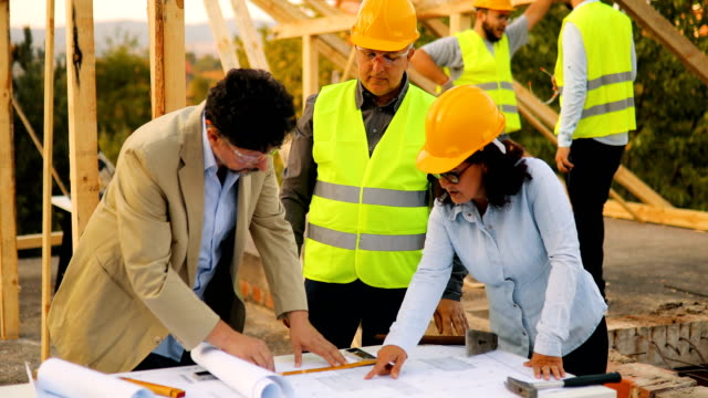 male and female architect discussing plans on site with the site manager and workers - architect stock videos & royalty-free footage