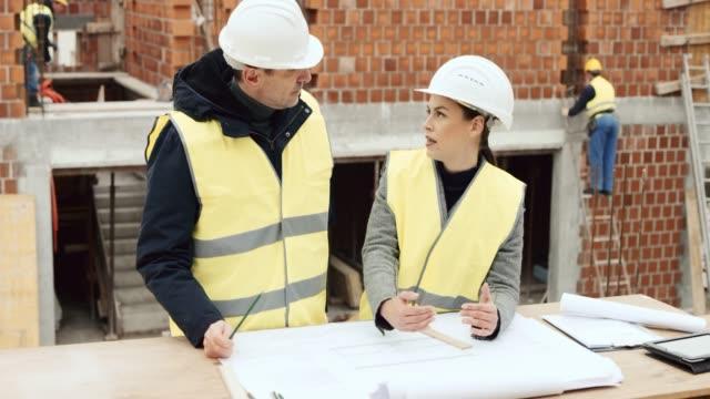 Männliche und weibliche Architekten zeichnen Details auf den Plan angelegt, auf der Baustelle