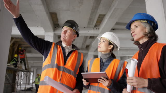 male and female architect having a discussion with the forewoman at the construction site of an industrial building - caposquadra video stock e b–roll