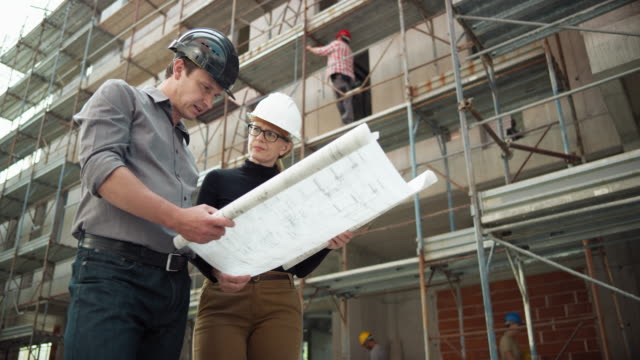 male and female architect looking at the plan outside at the construction site - tre quarti video stock e b–roll