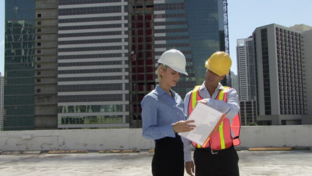 MS PAN Male and female architects looking at plans at construction site / Miami, Florida, USA