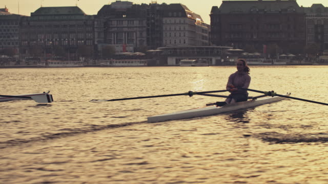 male and female are rowing boat in river at sunset - sculling stock videos & royalty-free footage