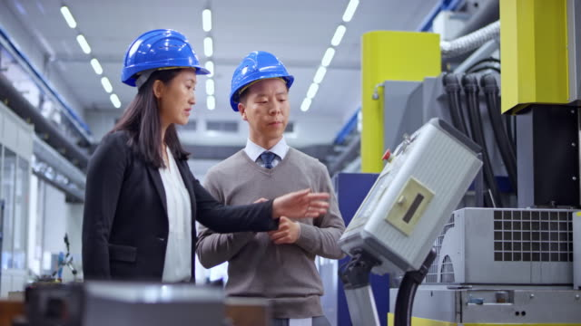 ds male and female asian engineer having a discussion standing by the machine in the factory - manufacturing machinery stock videos & royalty-free footage