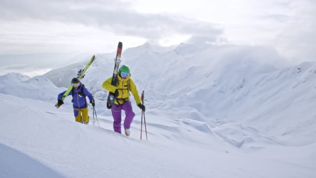 male and female backcountry skier carrying skis up the mountain - yellow stock videos & royalty-free footage