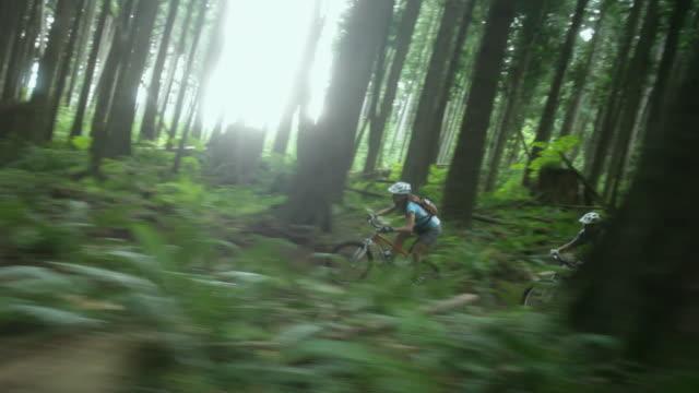 WS PAN Male and female biker mountain biking through forest / Squamish, British Columbia, Canada
