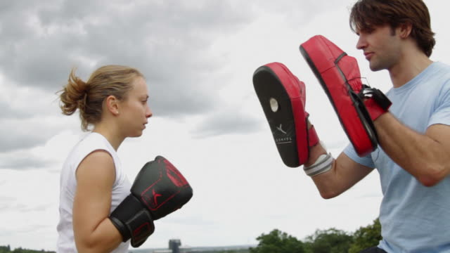 Male and female box training in park