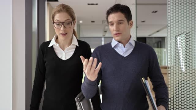 DS pour hommes et femmes et un collègue à parler dans le couloir