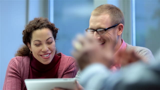 Male and female business partners point, laugh at something funny on tablet
