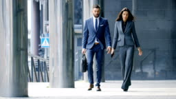 Male and Female Business People Walk and Discuss Financial Matters. They're Work in the Central Business District.