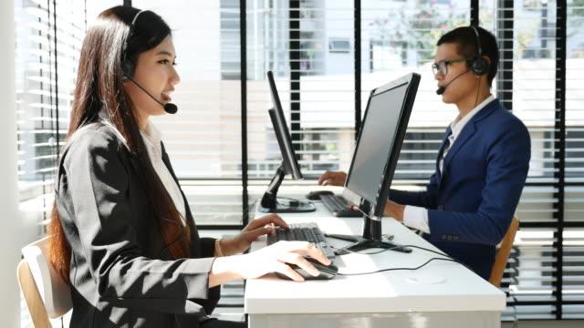 ヘッドセットを着ている男性と女性のコール センターの労働者 - サービス点の映像素材/bロール