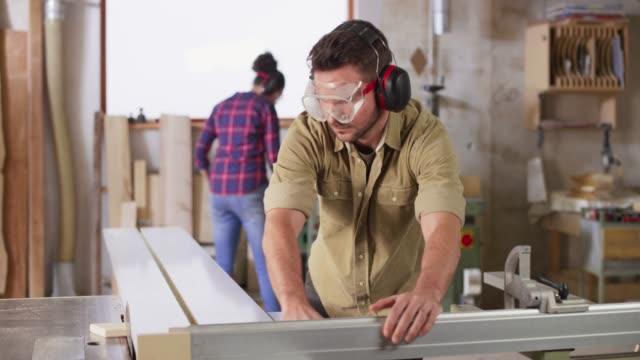 vídeos de stock e filmes b-roll de ds male and female carpenter working in the workshop - protetor de ouvido