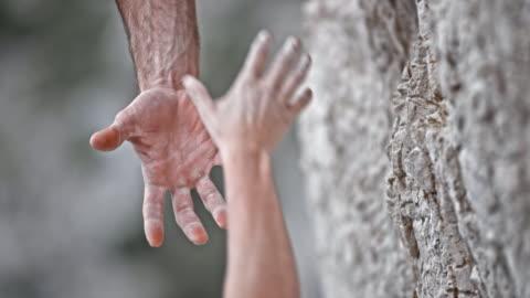 slo mo ld männliche und weibliche kletterer hand mit einander - herausforderung stock-videos und b-roll-filmmaterial