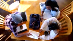 Male and female college students study for exam in coffee shop