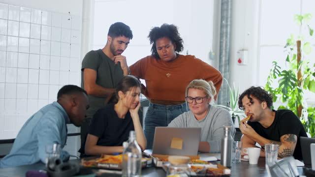 male and female computer programmers discussing over laptop during meeting at coworking office - kollega bildbanksvideor och videomaterial från bakom kulisserna