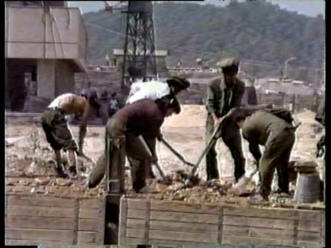 male and female construction workers toil on building site pyongyang; 26 aug 88 - erektion stock-videos und b-roll-filmmaterial