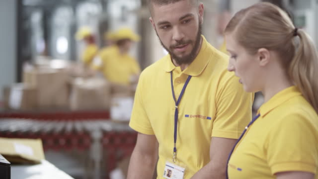 Male and female coworker checking the shipment documents in the warehouse before entering data into the computer