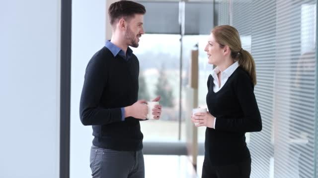 ld männliche und weibliche coworker trinken kaffee im flur - kaffeetasse stock-videos und b-roll-filmmaterial