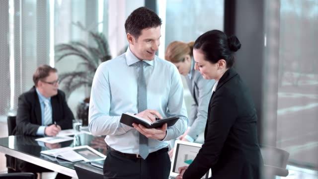 Homme et Femme collègue ayant une discussion dans la salle de conférence.