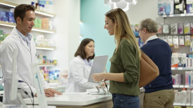 vídeos de stock, filmes e b-roll de clientes masculinos e fêmeas que compram medicinas na loja - farmácia