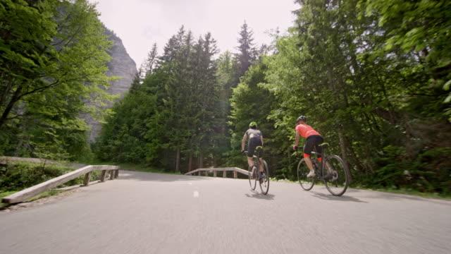 vídeos de stock e filmes b-roll de ts male and female cyclist riding road bikes up an asphalt mountain road in sunshine - bicicleta de corrida