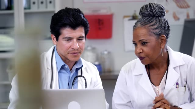 vídeos de stock, filmes e b-roll de médicos do sexo masculinos e femininos discutir o caso de um paciente - quadro médico