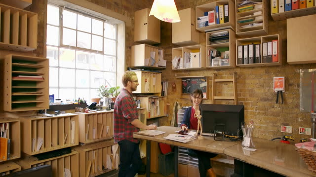 Male and female employees talk and discuss work in creative office space.