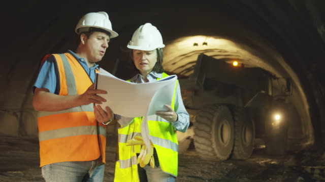 MS male and female engineer standing in tunnel, checking and discussing plans with dump trucks and tunnelling equipment operating in background