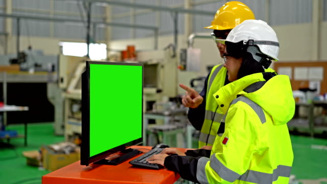 male and female engineer using a computer with green screen monitor working in a heavy industry manufacturing factory - steel stock videos & royalty-free footage