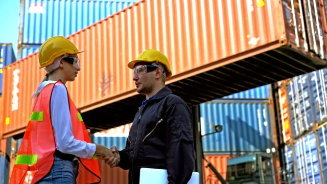 4k männlich und weiblich ingenieur mit sicherheitshelmen schütteln hände in versanddock - dockarbeiter stock-videos und b-roll-filmmaterial