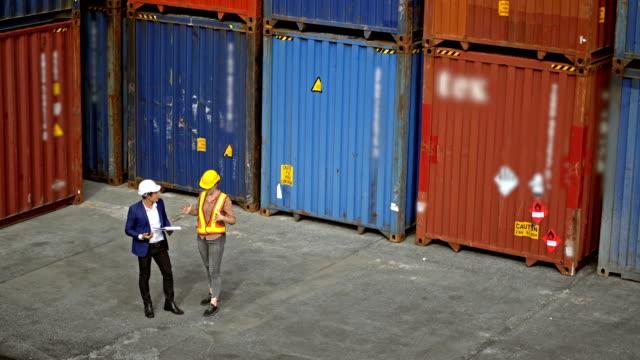 männliche und weibliche ingenieurin arbeitet mit frachtcontainern in einem kommerziellen schiffsdock - klemmbrett stock-videos und b-roll-filmmaterial