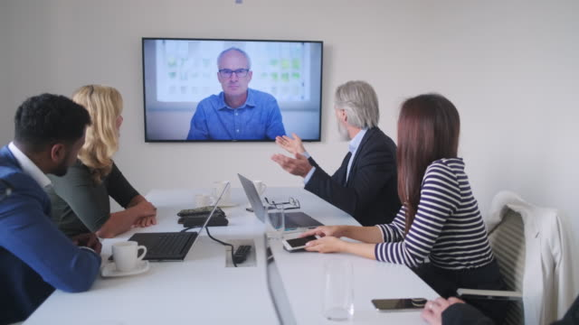 male and female executive team video conferencing with ceo - multi ethnic group stock videos & royalty-free footage